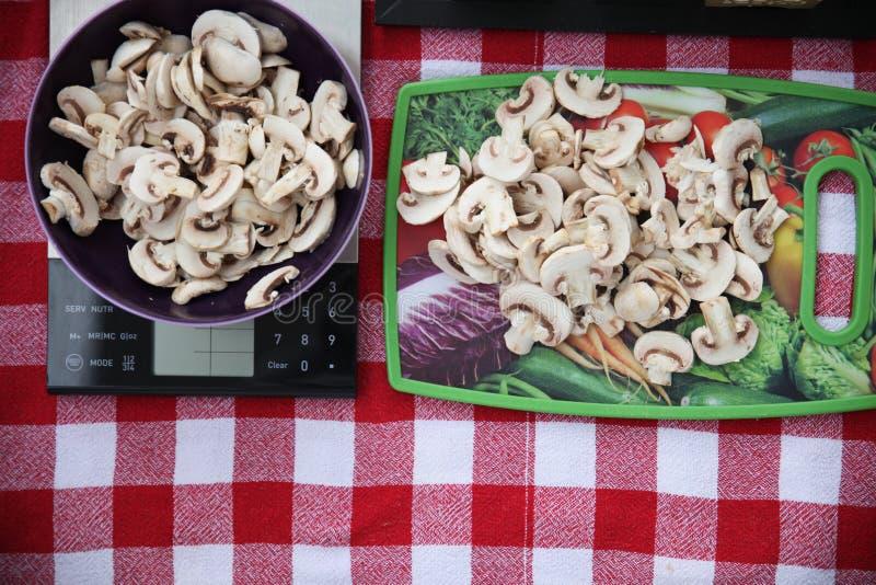 Πρόσφατα κόψτε τα μανιτάρια σε ένα κόκκινο και άσπρο τραπεζομάντιλο και προετοιμασμένος για το ψήσιμο ενός νόστιμου rucksa στοκ φωτογραφία
