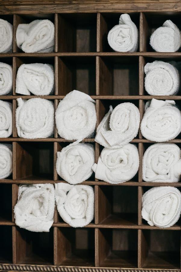Πρόσφατα πλυμένοι χνουδωτοί ρόλοι πετσετών σε ένα ξύλινο κομό Ευπρόσδεκτο ντεκόρ θερέτρου σε σε αργή κίνηση στοκ εικόνα