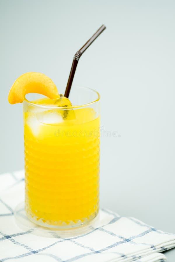 Πρόσφατα συμπιεσμένοι γλυκός χυμός από πορτοκάλι και διακόσμηση με το ροδάκινο φετών στοκ εικόνα