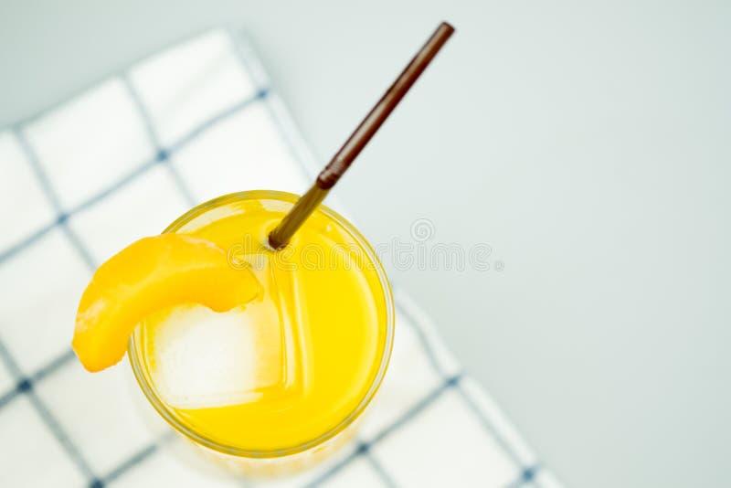 Πρόσφατα συμπιεσμένοι γλυκός χυμός από πορτοκάλι και διακόσμηση με το ροδάκινο φετών στοκ φωτογραφία