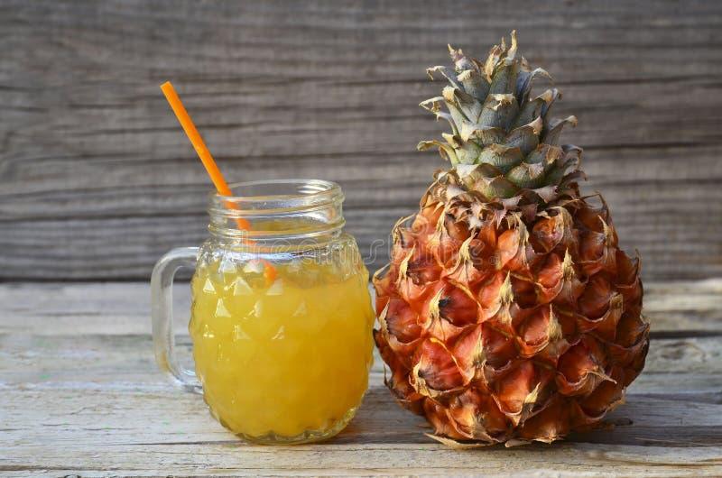 Πρόσφατα συμπιεσμένος χυμός ανανά σε ένα φλυτζάνι γυαλιού με το άχυρο κατανάλωσης και ώριμα φρούτα ανανάδων στον παλαιό ξύλινο πί στοκ φωτογραφίες με δικαίωμα ελεύθερης χρήσης