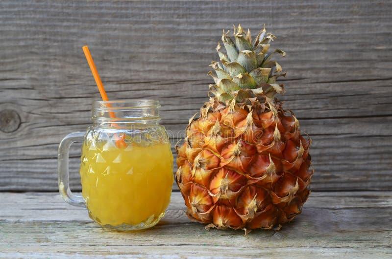 Πρόσφατα συμπιεσμένος χυμός ανανά σε ένα φλυτζάνι γυαλιού με το άχυρο κατανάλωσης και ώριμα φρούτα ανανάδων στον παλαιό ξύλινο πί στοκ φωτογραφία