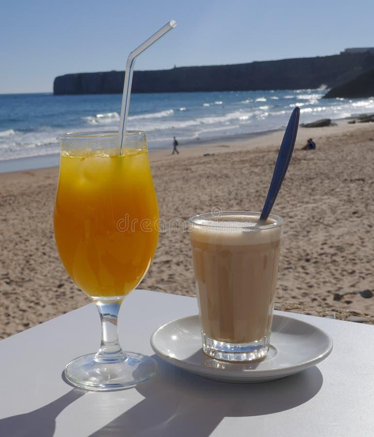 Πρόσφατα συμπιεσμένος χυμός από πορτοκάλι και ένα γυαλί του latte σε έναν μικρό φραγμό παραλιών που αγνοεί τη θάλασσα στοκ εικόνες
