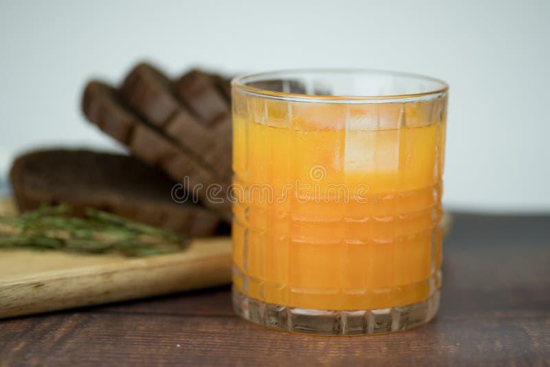 Πρόσφατα συμπιεσμένος χυμός από πορτοκάλι με τους κύβους πάγου στο γυαλί στοκ εικόνες