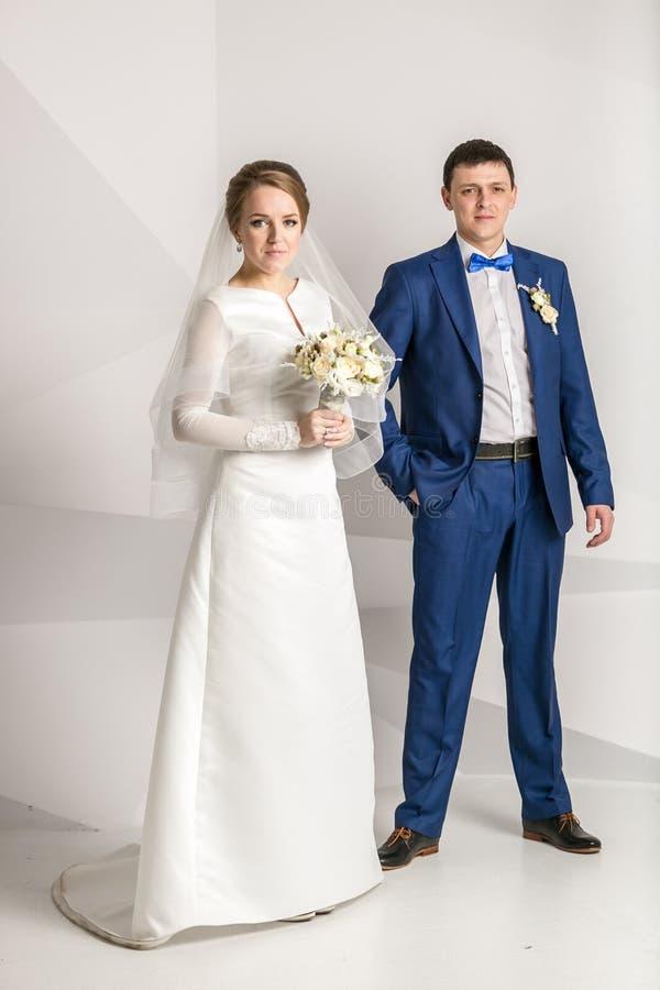 Πρόσφατα τοποθέτηση παντρεμένων ζευγαριών στο στούντιο πέρα από το άσπρο υπόβαθρο στοκ φωτογραφία