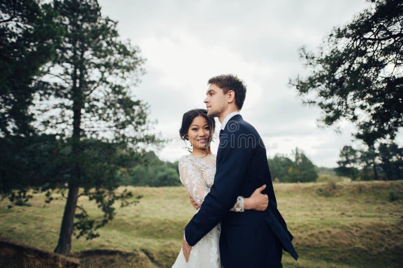 Πρόσφατα το ζεύγος που φιλά tenderly μεταξύ των κομψών δέντρων στοκ φωτογραφίες με δικαίωμα ελεύθερης χρήσης