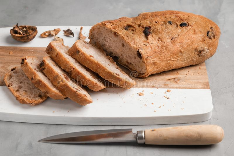 Πρόσφατα υγιές τεμαχισμένο ψωμί με τα ξύλα καρυδιάς και τις σταφίδες στον τέμνοντα πίνακα στο γκρίζο υπόβαθρο πετρών στοκ εικόνες