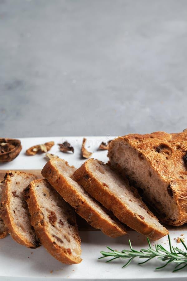 Πρόσφατα υγιές τεμαχισμένο ψωμί με τα ξύλα καρυδιάς και τις σταφίδες στον τέμνοντα πίνακα στο γκρίζο υπόβαθρο πετρών στοκ φωτογραφία