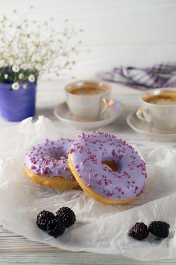Πρόσφατα ψήνει το βατόμουρο donuts με τον καφέ και την κρέμα, ρύθμιση προγευμάτων πρωινού στοκ εικόνες