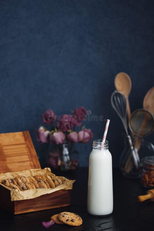Πρόσφατα ψημένα μπισκότα και μπουκάλι τσιπ αμυγδάλων σοκολάτας με το γάλα στοκ εικόνα