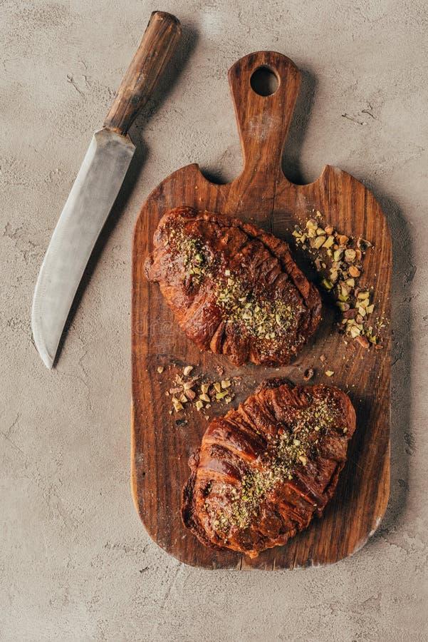 πρόσφατα ψημένος croissants με τα καρύδια φυστικιών στον ξύλινο τέμνοντα πίνακα και το μαχαίρι στην ελαφριά επιφάνεια στοκ εικόνα