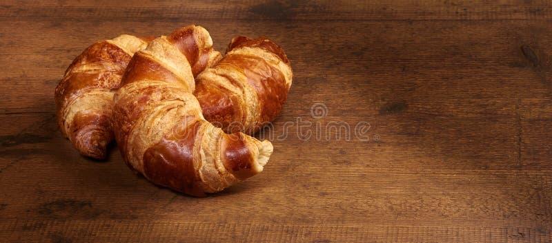 Πρόσφατα ψημένος croissants στον ξύλινο τέμνοντα πίνακα, κινηματογράφηση σε πρώτο πλάνο στοκ φωτογραφίες