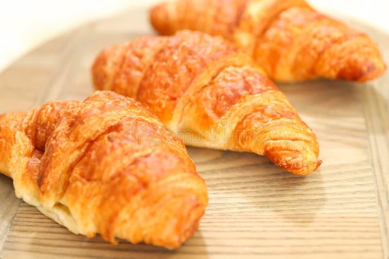 Πρόσφατα ψημένος croissants στον ξύλινο τέμνοντα πίνακα, τοπ άποψη στοκ εικόνες
