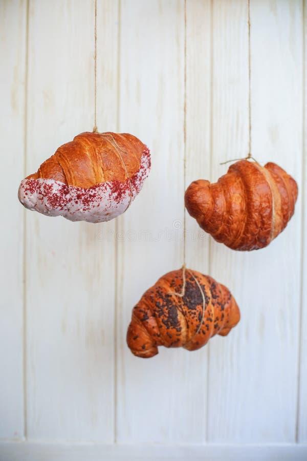 Πρόσφατα ψημένος croissants στον ξύλινο τέμνοντα πίνακα, τοπ άποψη στοκ φωτογραφία