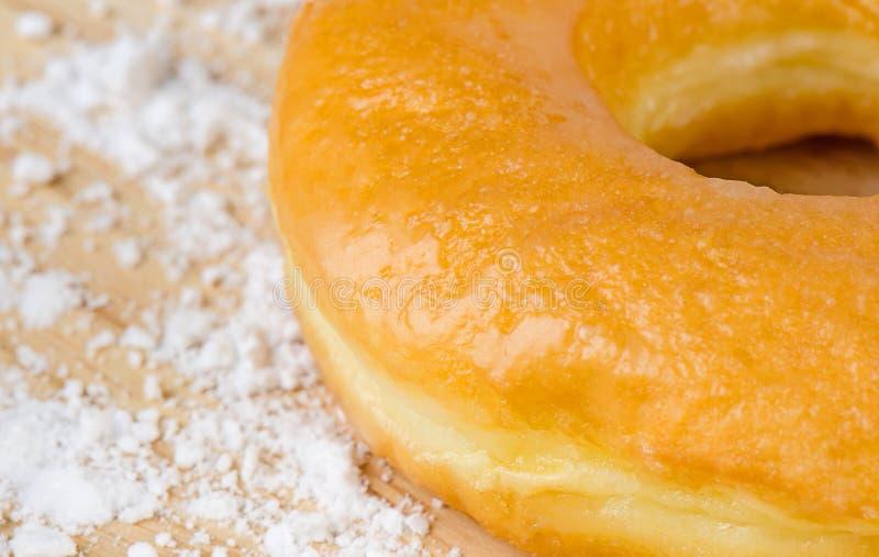 Πρόσφατα ψημένος donuts με τη ζάχαρη τήξης στο ξύλινο υπόβαθρο στοκ εικόνες