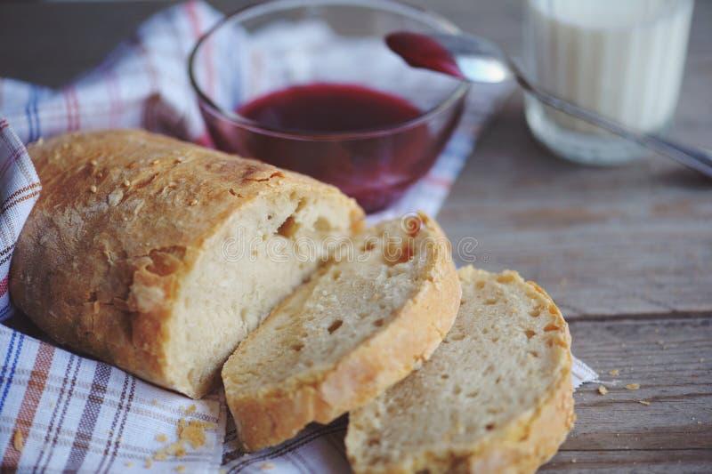 Πρόσφατα ψημένο ψωμί που εξυπηρετείται με τη μαρμελάδα και το ποτήρι του γάλακτος στοκ εικόνα