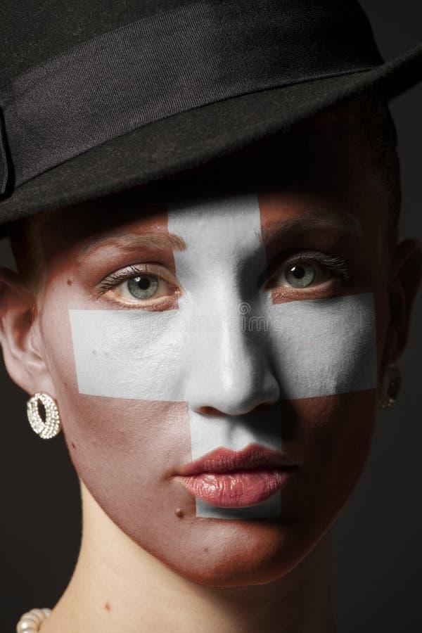 Πρόσωπο γυναικών με τη χρωματισμένη ελβετική σημαία στοκ εικόνα με δικαίωμα ελεύθερης χρήσης