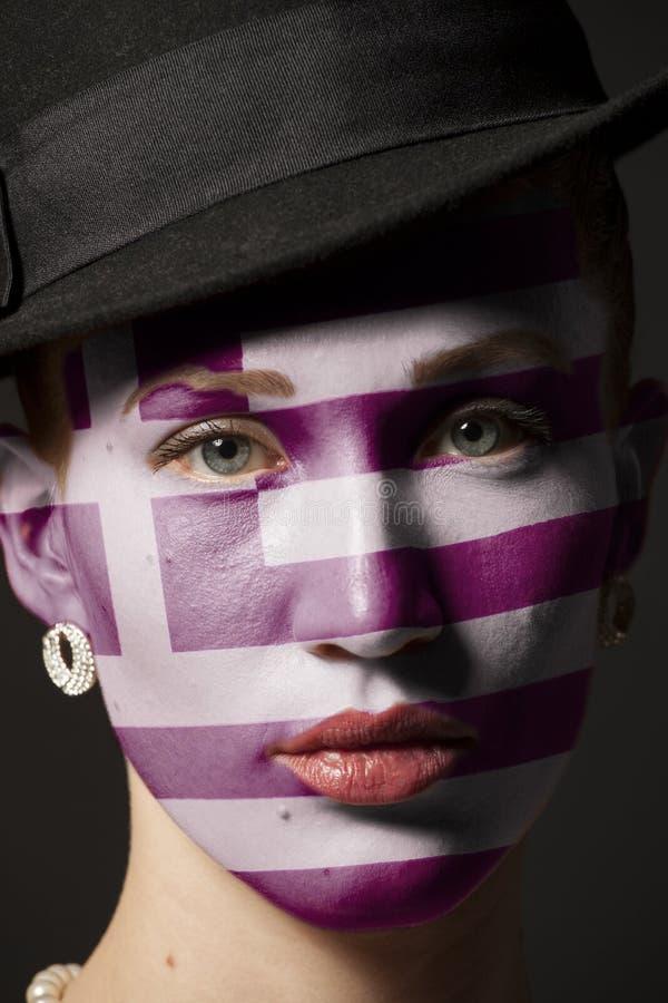 Πρόσωπο γυναικών με τη χρωματισμένη σημαία της Ελλάδας στοκ φωτογραφία με δικαίωμα ελεύθερης χρήσης