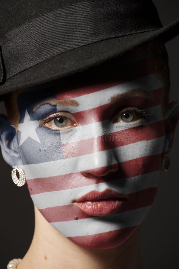 Πρόσωπο γυναικών με τη χρωματισμένη σημαία της Λιβερίας στοκ φωτογραφία