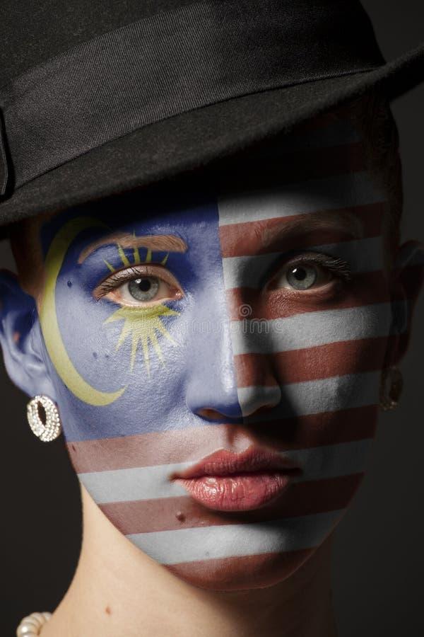 Πρόσωπο γυναικών με τη χρωματισμένη σημαία της Μαλαισίας στοκ φωτογραφίες