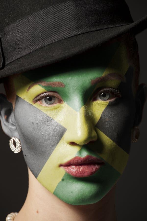 Πρόσωπο γυναικών με τη χρωματισμένη σημαία της Τζαμάικας στοκ φωτογραφία με δικαίωμα ελεύθερης χρήσης