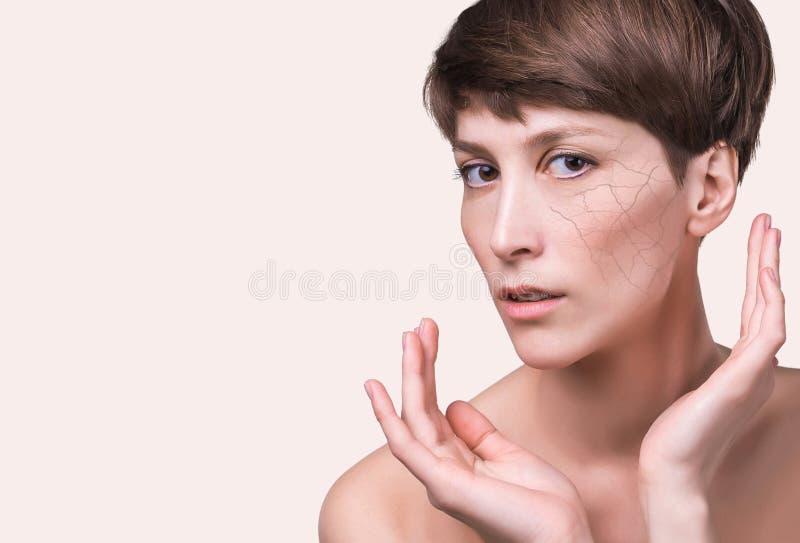 Πρόσωπο γυναικών που καλύπτεται με το ραγισμένο σύμβολο γήινης σύστασης του ξηρού δέρματος στοκ φωτογραφία με δικαίωμα ελεύθερης χρήσης