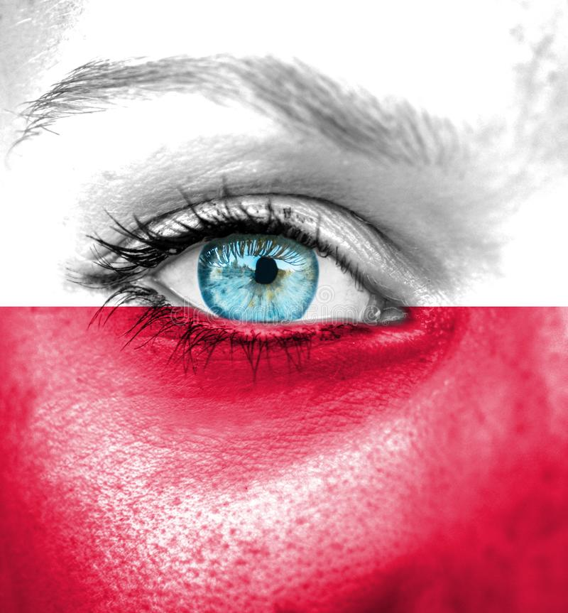 Πρόσωπο γυναικών που χρωματίζεται με τη σημαία της Πολωνίας στοκ εικόνα