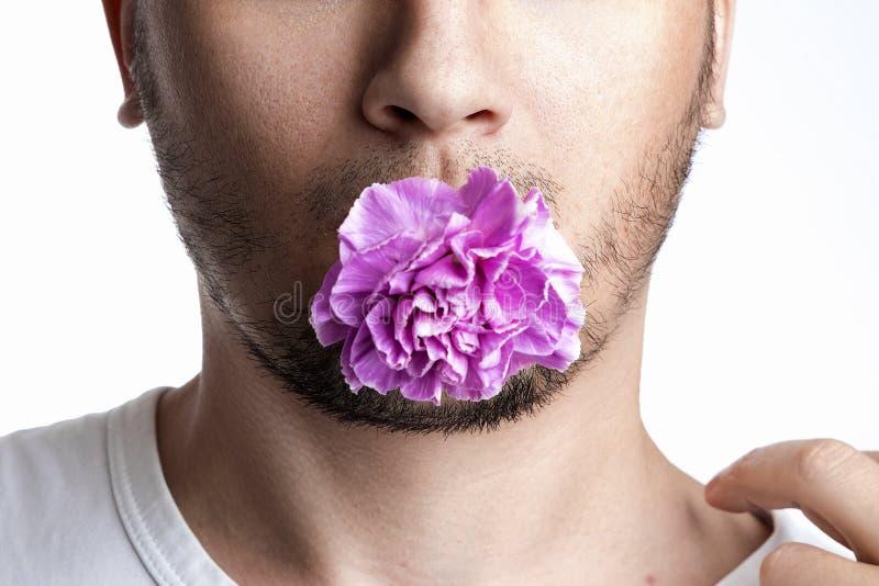 Πρόσωπο ενός ανθρώπου με ένα μωβ άνθος ενός γαρύφαλλου στο στόμα, ένα λουλούδι στο στόμα ενός ανθρώπου σε λευκό φόντο Κοντινό Η στοκ φωτογραφία με δικαίωμα ελεύθερης χρήσης
