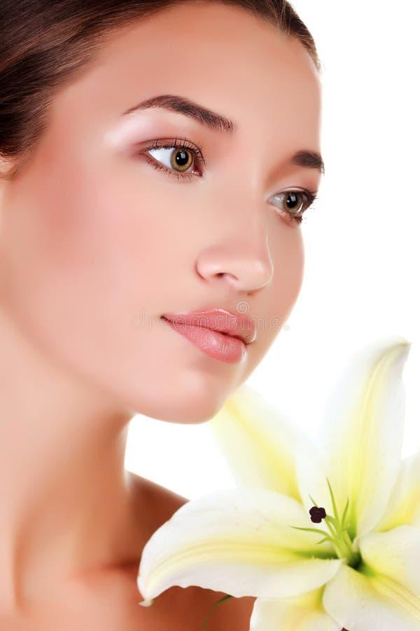 Πρόσωπο ενός όμορφου κοριτσιού με έναν φρέσκο κρίνο λουλουδιών στοκ φωτογραφίες με δικαίωμα ελεύθερης χρήσης