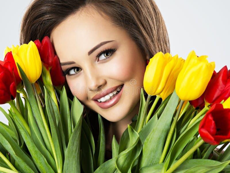 Πρόσωπο κινηματογραφήσεων σε πρώτο πλάνο της όμορφης ευτυχούς γυναίκας με τα λουλούδια στοκ φωτογραφίες