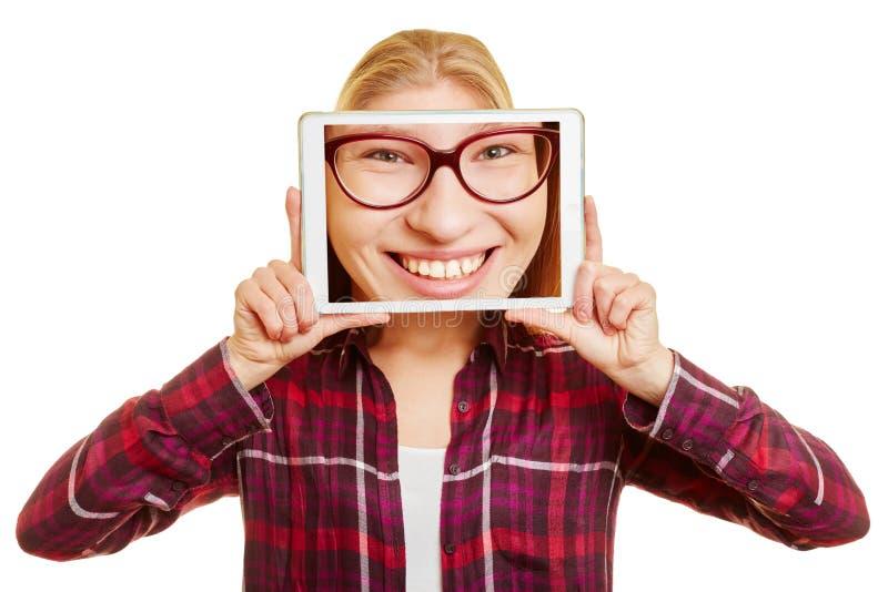 Πρόσωπο μιας γυναίκας σε μια ταμπλέτα στοκ φωτογραφία