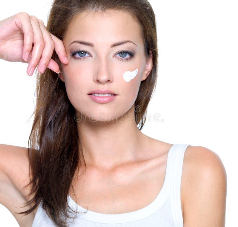 Πρόσωπο μιας νέας γυναίκας με την κρέμα στο πρόσωπο στοκ εικόνα με δικαίωμα ελεύθερης χρήσης