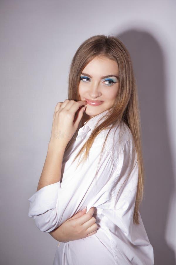 Πρόσωπο μιας όμορφης νέας γυναίκας με τα φωτεινά μπλε μάτια στοκ φωτογραφία