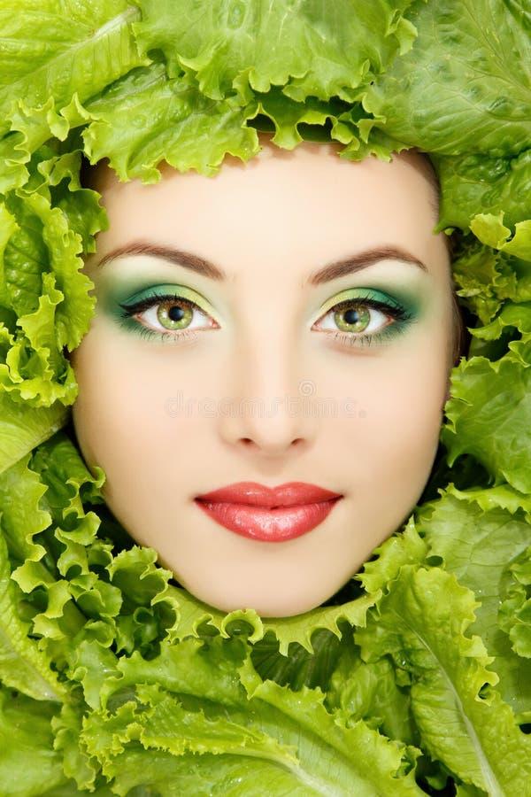 Πρόσωπο ομορφιάς γυναικών με τα πράσινα φρέσκα φύλλα μαρουλιού στοκ εικόνες