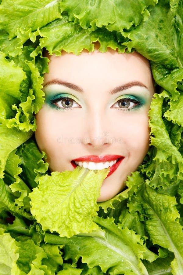 Πρόσωπο ομορφιάς γυναικών με τα πράσινα φρέσκα φύλλα μαρουλιού στοκ φωτογραφία με δικαίωμα ελεύθερης χρήσης