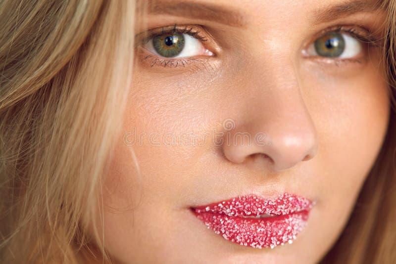 Πρόσωπο ομορφιάς Η όμορφη γυναίκα με τα πλήρη χείλια με το χείλι ζάχαρης τρίβει στοκ φωτογραφίες