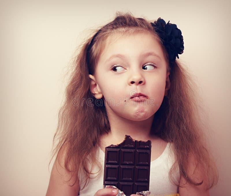 Πρόσωπο παιδιών χιούμορ σκέψης που τρώει τη σοκολάτα Τρύγος κινηματογραφήσεων σε πρώτο πλάνο στοκ εικόνες με δικαίωμα ελεύθερης χρήσης