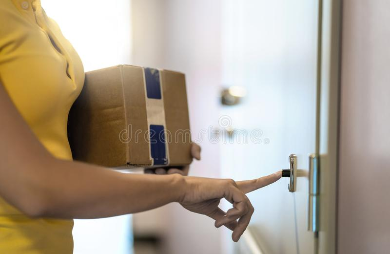 Πρόσωπο παράδοσης που παραδίδει τη συσκευασία στην εγχώρια πόρτα Υπηρεσία αποστολών Γυναίκα που χτυπά doorbell στοκ εικόνες