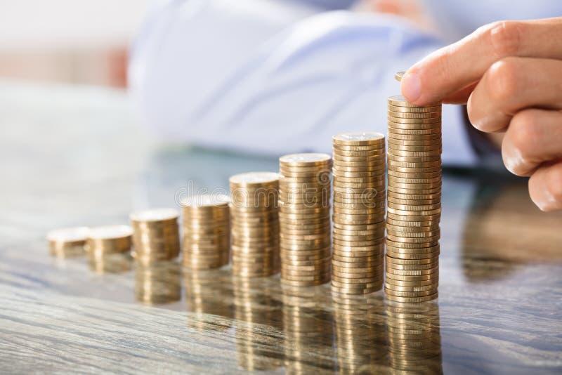 Πρόσωπο που τοποθετεί το νόμισμα πέρα από το σωρό νομισμάτων στοκ εικόνες