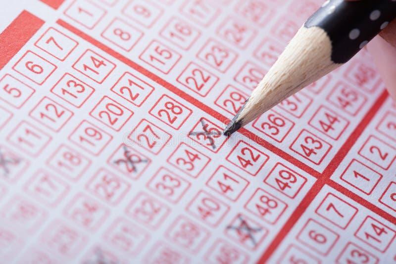 Πρόσωπο που χαρακτηρίζει τον αριθμό στο εισιτήριο λαχειοφόρων αγορών στοκ φωτογραφία με δικαίωμα ελεύθερης χρήσης