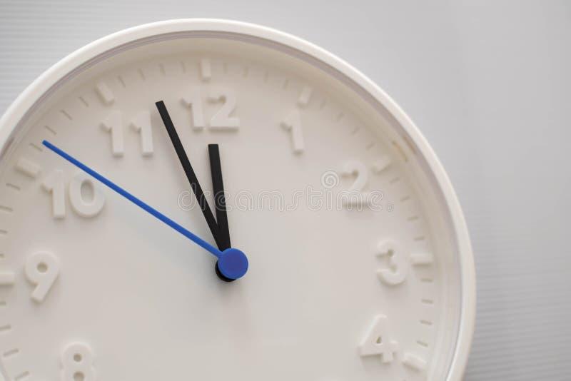 Πρόσωπο ρολογιών που παρουσιάζει δώδεκα η ώρα με το άσπρο υπόβαθρο Άσπρο στρογγυλό ρολόι τοίχων Δώδεκα η ώρα Μεσημβρία ή μεσάνυχτ στοκ φωτογραφία