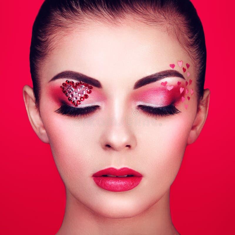 Πρόσωπο της όμορφης γυναίκας με την καρδιά διακοπών makeup στοκ φωτογραφία