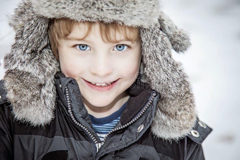 Πρόσωπο του ευτυχούς αγοριού στο χειμερινό καπέλο στοκ εικόνες
