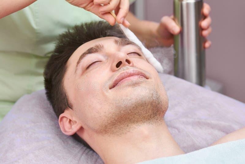Πρόσωπο του νεαρού άνδρα, cryomassage στοκ εικόνα