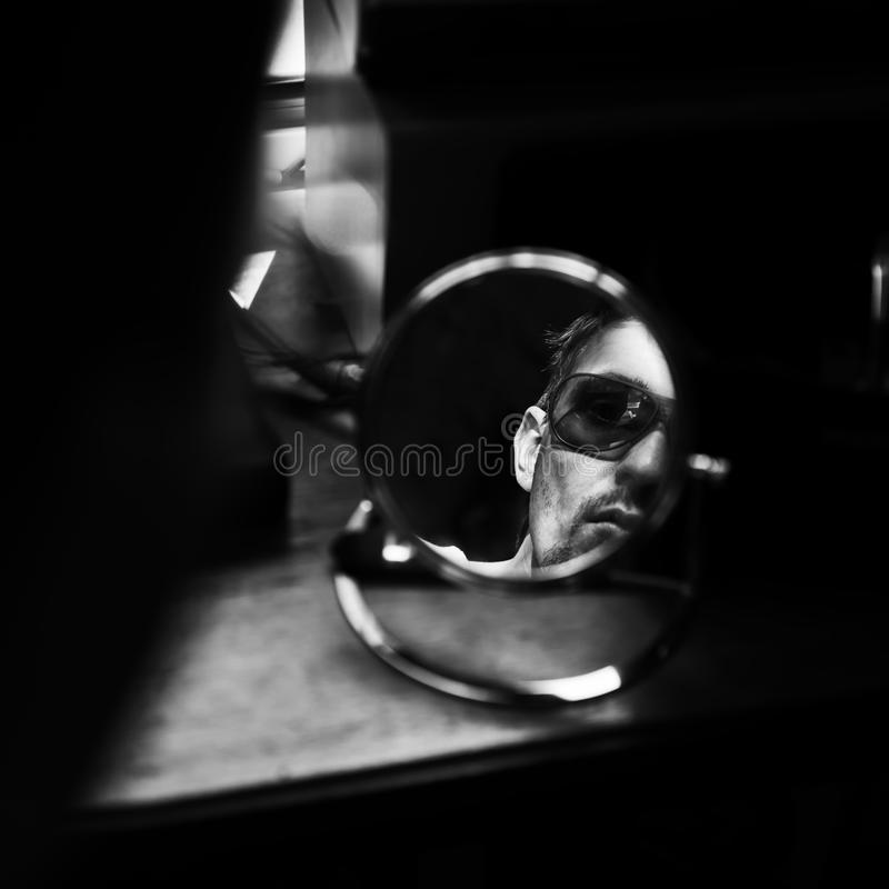 Πρόσωπο του νεαρού άνδρα στο μικρό στρογγυλό καθρέφτη στοκ φωτογραφίες