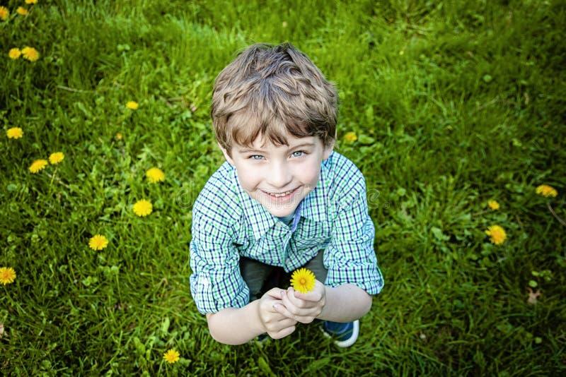 Πρόσωπο του χαμογελώντας ευτυχούς αγοριού έξω από τα λουλούδια επιλογής στοκ εικόνα με δικαίωμα ελεύθερης χρήσης