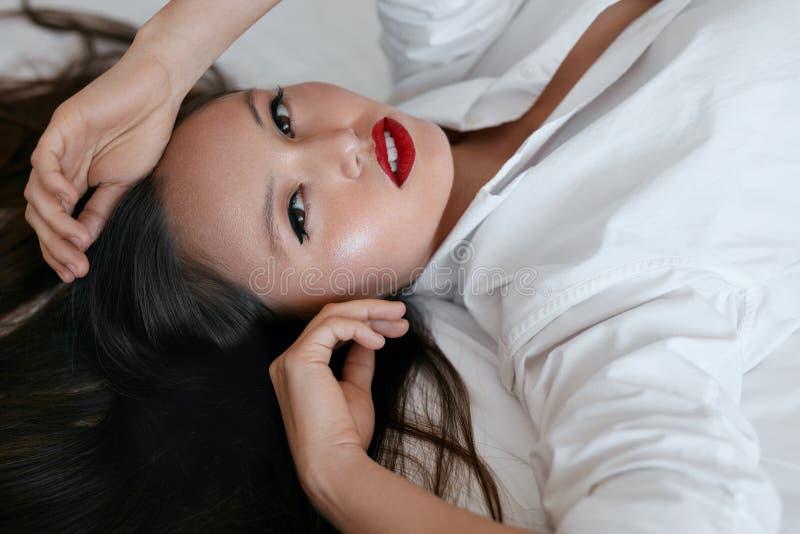 Πρόσωπο Makeup ομορφιάς Όμορφη γυναίκα με τη μαύρη τρίχα και τα κόκκινα χείλια στοκ φωτογραφία