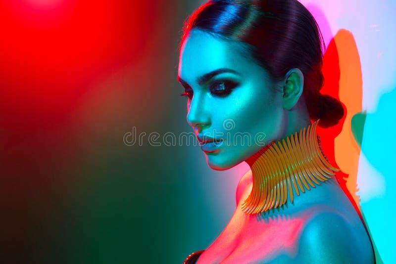 Πρότυπη γυναίκα μόδας στη ζωηρόχρωμη φωτεινή τοποθέτηση φω'των στοκ φωτογραφίες