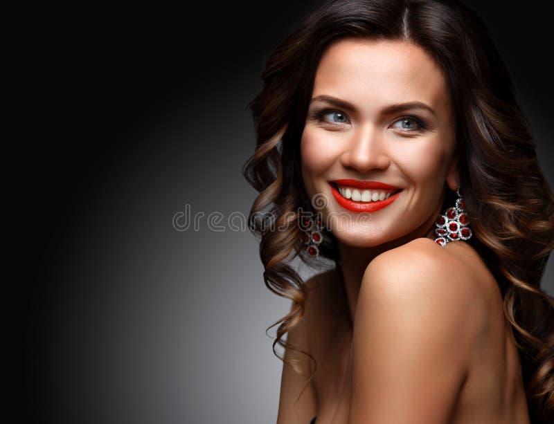 Πρότυπη γυναίκα ομορφιάς με τη μακριά καφετιά κυματιστή τρίχα Υγιής τρίχα και όμορφο επαγγελματικό Makeup Κόκκινα χείλια και καπν στοκ εικόνα