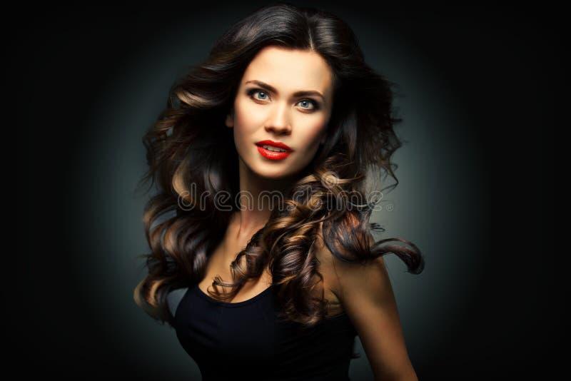 Πρότυπη γυναίκα ομορφιάς με τη μακριά καφετιά κυματιστή τρίχα Υγιής τρίχα και όμορφο επαγγελματικό Makeup Κόκκινα χείλια και καπν στοκ φωτογραφία
